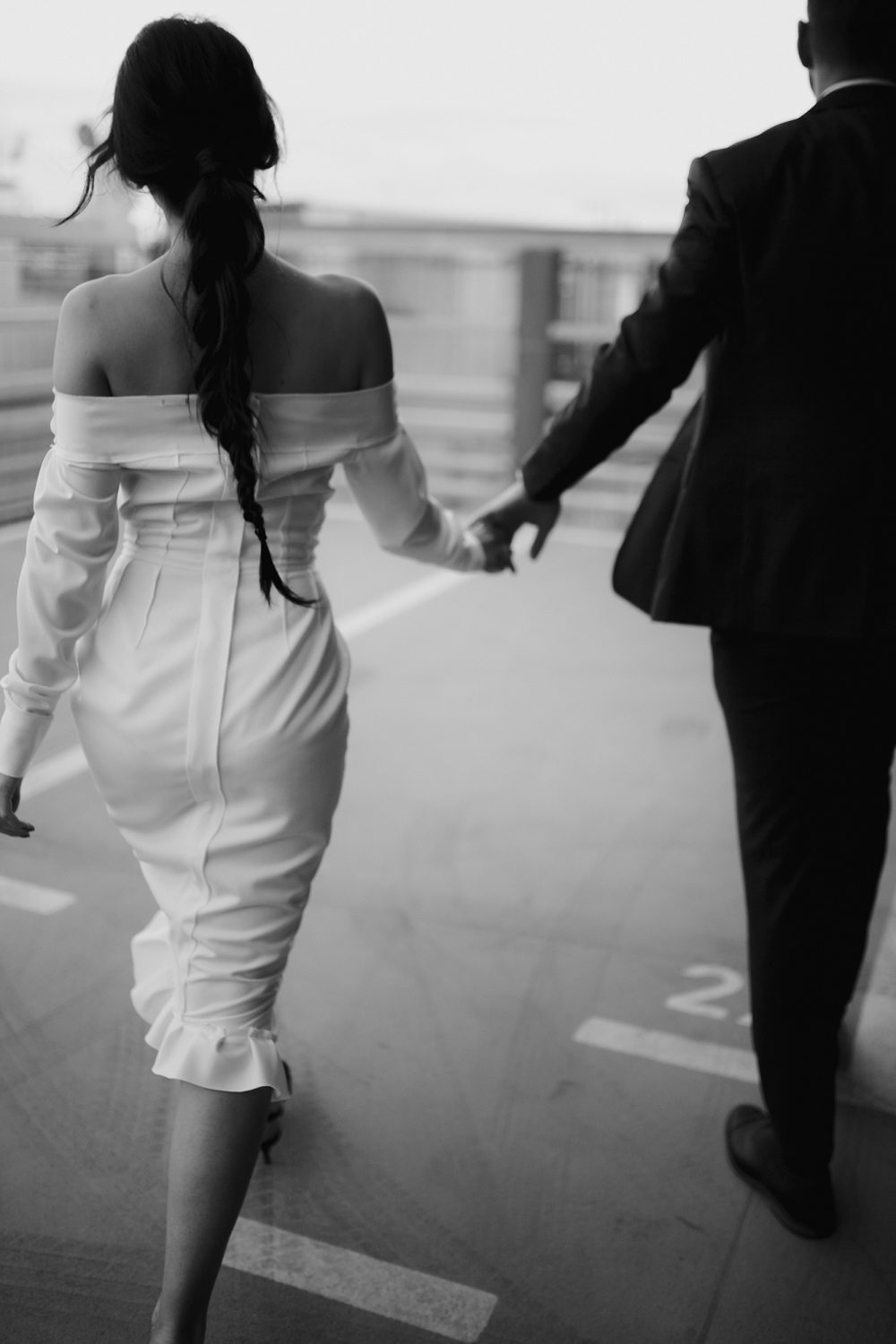 black and white photo of bride and groom walking on Belgrade rooftop